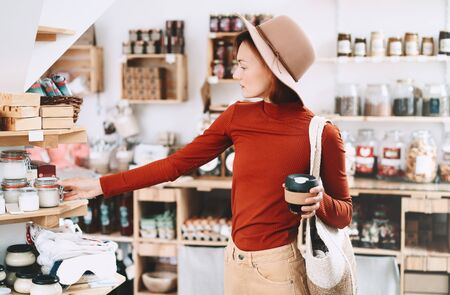 Photo pour Young woman choosing products in zero waste shop. Minimalist style girl with wicker bag buying personal hygiene items in plastic free store. Customer doing shopping without plastic packaging. - image libre de droit