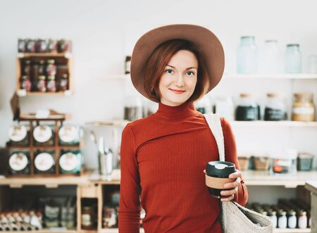 Foto de Minimalist vegan style girl with wicker bag and reusable glass coffee cup on background of interior of zero waste shop. Woman doing shopping without plastic packaging in plastic free grocery store. - Imagen libre de derechos