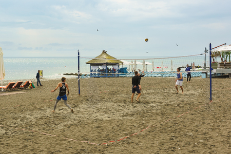 Sochi, Krasnodar Krai, Russia - June 07.2017: Young people playing beach volleyball on the sand at the Black sea