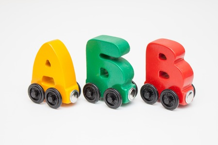 Foto de Russian wooden letters train alphabet with locomotive. Bright colors of red yellow green and blue on a white background. Early childhood education, learning to read, preschool and kids game concept - Imagen libre de derechos