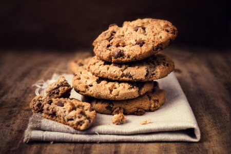 Photo for Chocolate cookies on white linen napkin on wooden table. Chocolate chip cookies shot on coffee colored cloth, closeup. - Royalty Free Image