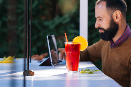 Foto de Bearded man in a cafe drinking mulled wine. Businessman works in office, holds a glass with a red hot drink and uses tablet. - Imagen libre de derechos