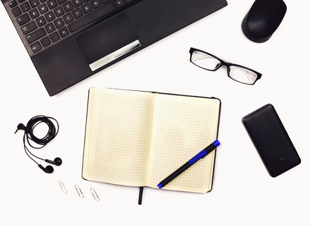 Photo for Workplace flat lay with laptop, glasses, headphones, mobile phone and and opened notebook with a pen. Office tools. White background. - Royalty Free Image