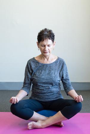 Foto für Older woman in black and grey yoga clothing meditating on pink mat - Lizenzfreies Bild