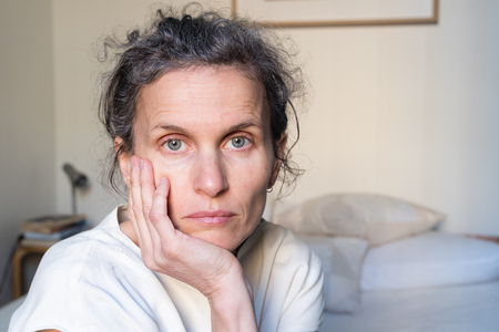 Photo for Portrait of despondent middle aged woman in bedroom (selective focus) - Royalty Free Image