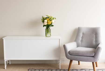 Foto de Grey retro armchair next to white sideboard with glass jar of cream and yellow flowers against neutral wall background - Imagen libre de derechos