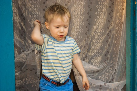 Foto de In early spring, in the village, a small blond boy of three years old, chumazenky, comes out of his village house, whose door is covered with insect tulle. - Imagen libre de derechos