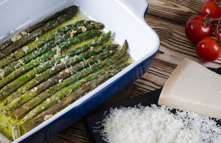 Photo pour Green juicy asparagus is in ceramic form in olive oil sprinkled with parmesan and garlic. - image libre de droit