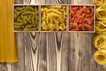 Photo pour Multi-coloured pasta in the form of spirals lies in square wooden boxes that stand on a wooden table - image libre de droit
