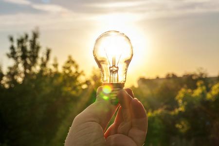 Foto de The light bulb in her hand against the dawn. Symbol, concept of new creative business idea. Eco energy Save - Imagen libre de derechos