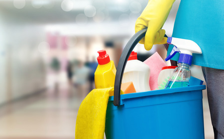 Foto de Cleaning lady with a bucket and cleaning products on blurred background. - Imagen libre de derechos