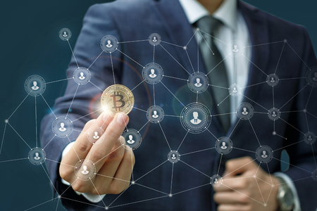 Foto de Businessman is holding a bitcoin as part of a business network on blue background. - Imagen libre de derechos