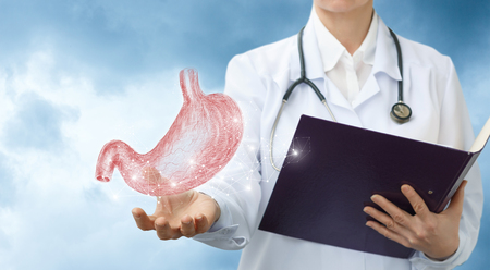 Photo for Doctor gastroenterologist shows the stomach against the sky. - Royalty Free Image