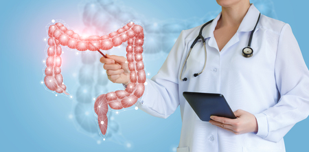 Photo for Doctor shows colon on virtual screen over blue background. - Royalty Free Image