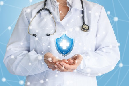 Foto de Doctor shows the symbol of protection of health on a blue background. - Imagen libre de derechos