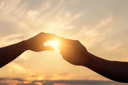 Foto de Holding Hands in the background of the sunset. - Imagen libre de derechos