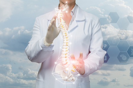 Foto de A doctor is operating with an artificial spine with pelvis unite inside digital wireless connections cage at the comb medical service system background. A concept of spine diseases treatment. - Imagen libre de derechos