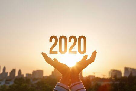 Foto de The concept new 2020 year. Hands show 2020 on the background of sunset. - Imagen libre de derechos