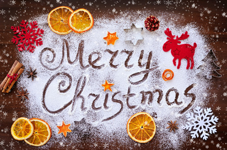 Foto de Merry Christmas text made with flour with decorations on cutting board - Imagen libre de derechos