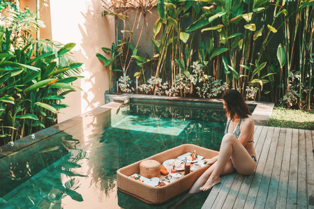 Photo for A young girl in a swimsuit is having breakfast in the pool at a private villa - Royalty Free Image