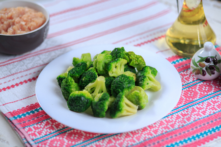Crude broccoli on a white plate on a light background
