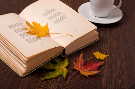 Foto de Cup of coffee, book and autumn leaves on wooden table. Autumn concept. - Imagen libre de derechos