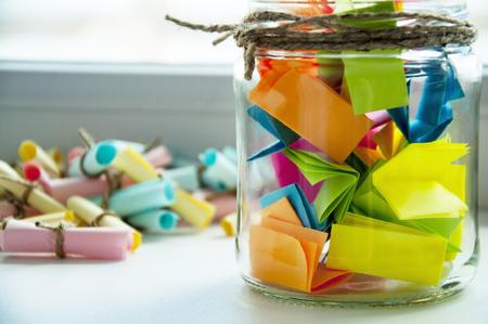 Foto de Glass jar with colored notes with blur and toning - Imagen libre de derechos