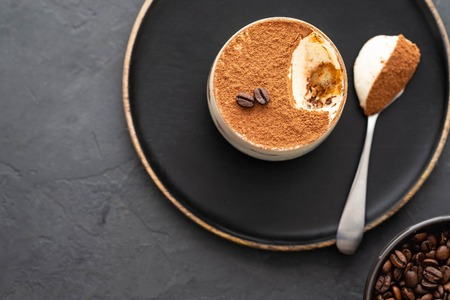 Photo for Delicious Italian dessert tiramisu, chocolate, cocoa and coffee beans on a black background. Top view with copy space. - Royalty Free Image