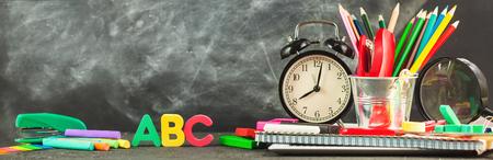Foto de Banner Back to school Accessories for school on a dark background Pencils Plasticine letters Letters Alarm clock Chalk Copy space. - Imagen libre de derechos