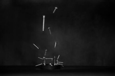 Foto de The concept of levitation of the object.Demonstration of magnetism - metal chrome nails and screws are attracted to a round magnet on a dark background.Selective focus,black minimalism,space for text - Imagen libre de derechos