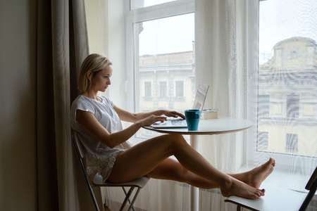 Photo for Young attractive girl sitting near big window with coffee and working on laptop. - Royalty Free Image