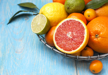 Photo for Different fresh citrus fruit in a basket on a blue wooden background - Royalty Free Image
