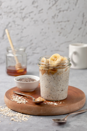 Photo for healthy diet breakfast. overnight oatmeal with chia seeds, bananas, peanut butter, honey in a glass jar on a gray concrete background - Royalty Free Image