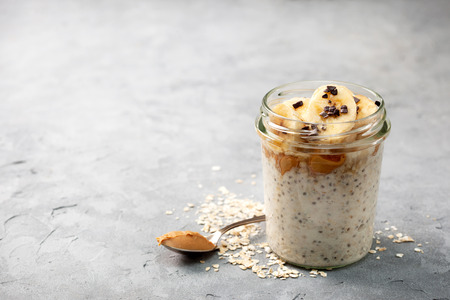 Photo for healthy diet breakfast. overnight oatmeal with chia seeds, bananas, peanut butter, honey, chocolate sprinkling in a glass jar on a gray concrete background - Royalty Free Image