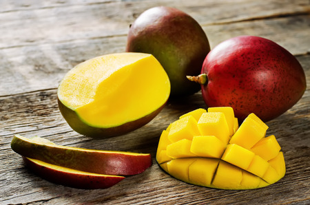 Foto de mango on a dark wood background. tinting. selective focus on the mangos slices - Imagen libre de derechos