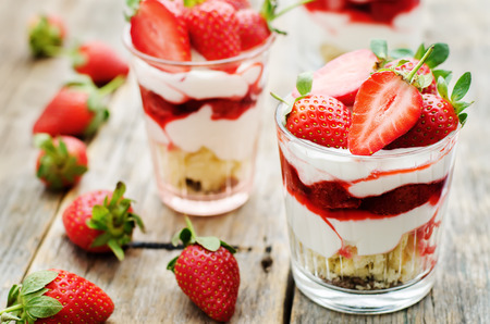 Photo for layered dessert with strawberries, biscuit cake and cream cheese on a dark wood background. tinting. selective focus - Royalty Free Image