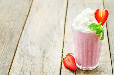 Foto de strawberry milkshake with whipped cream on a dark wood background. tinting. selective focus - Imagen libre de derechos