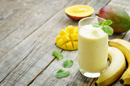 Foto de banana mango smoothie on a dark wood background - Imagen libre de derechos