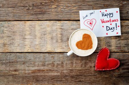 Foto de card for Valentines day, red toy heart and a cup of coffee on a dark wood background. toning. selective Focus - Imagen libre de derechos