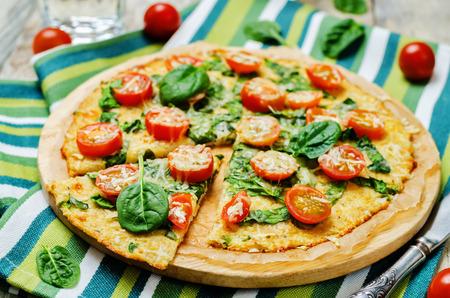 Foto de Cauliflower pizza crust with tomato and spinach. toning. selective focus - Imagen libre de derechos