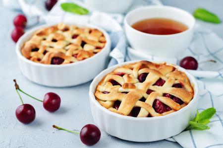 Photo pour Cherry pies with fresh cherries on a grey background. tonung. selective focus - image libre de droit