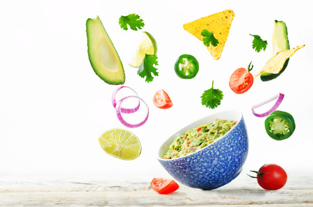 Foto per Guacamole with flying corn chips and ingredients to prepare it on a white background. toning. selective focus - Immagine Royalty Free