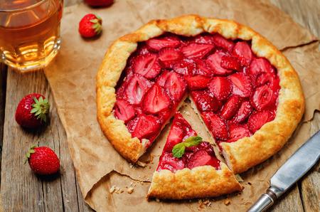 Foto de Strawberry galette with fresh strawberries on a wood background. toning. selective focus - Imagen libre de derechos