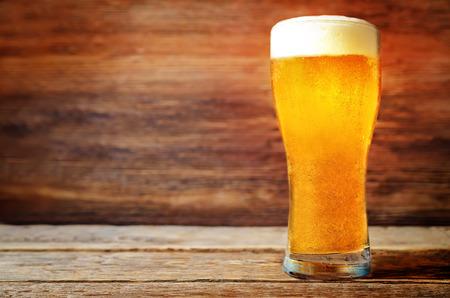 Foto de Glass of cold light beer on a wood  background. toning. selective focus - Imagen libre de derechos