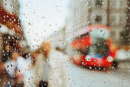 Foto per Raindrop on glass and red London bus lights blurry background. - Immagine Royalty Free