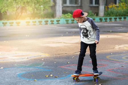 Foto de Little urban boy with a penny skateboard. Young kid riding in the park on a skateboard. City style. Urban kids. Child learns to ride a penny board - Imagen libre de derechos