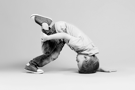 Photo pour break dance kids. little break dancer showing his skills in dance studio. Hip hop dancer boy performing over studio background. Black and white photography - image libre de droit