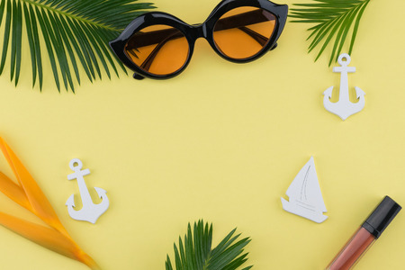 Foto de Sunglasses and lip gloss decorate with tiny sailboat, anchor, bird of paradise flower and fern leaves on yellow background with copy space - Imagen libre de derechos