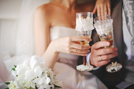 Foto de bride and groom holding beautifully decorated wedding glasses with champaign - Imagen libre de derechos