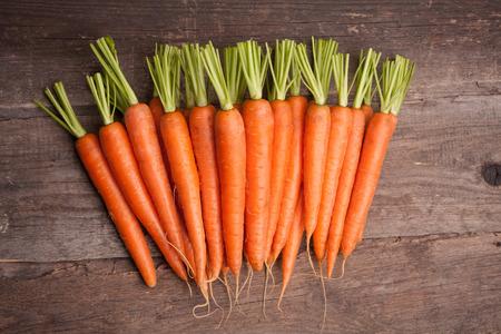 Photo pour fresh carrot bunch on grungy wooden background - image libre de droit